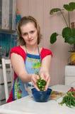 Jonge vrouw die vegetarische plantaardige salade maakt Stock Afbeeldingen