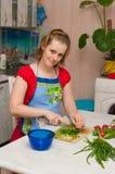 Jonge vrouw die vegetarische plantaardige salade maakt Stock Foto's