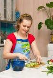 Jonge vrouw die vegetarische plantaardige salade maakt Royalty-vrije Stock Foto