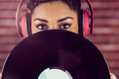 Jonge vrouw die verbergen achter vinyl Royalty-vrije Stock Afbeelding