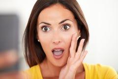 Jonge vrouw die verrast terwijl het gebruiken van mobiel kijken stock fotografie