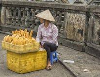 Jonge vrouw die vers gebakken brood in de straat verkopen. Royalty-vrije Stock Foto's
