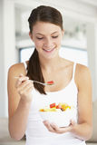 Jonge Vrouw die Verse Fruitsalade eet Stock Afbeeldingen