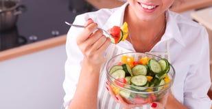 Jonge vrouw die verse salade in moderne keuken eten Royalty-vrije Stock Fotografie