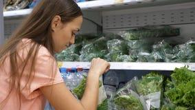 Jonge vrouw die verse sla selecteren bij kruidenierswinkelafdeling bij winkelcomplex Royalty-vrije Stock Afbeeldingen