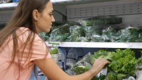 Jonge vrouw die verse sla selecteren bij kruidenierswinkelafdeling bij winkelcomplex Royalty-vrije Stock Fotografie