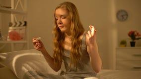 Jonge vrouw die vingers kruisen die de hand van de zwangerschapstest houden, geboortenbeperkingsmethodes stock footage