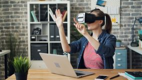 Jonge vrouw die virtuele werkelijkheidsglazen gebruiken bij het werk bewegende handen tijdens onderbreking stock videobeelden
