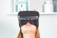 Jonge vrouw die virtuele werkelijkheidsglazen thuis dragen Stock Foto's