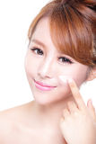 Jonge vrouw die vochtinbrengende crèmeroom op gezicht toepassen Royalty-vrije Stock Foto's