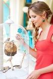 Jonge vrouw die vogels in witte kooi bekijkt Royalty-vrije Stock Foto's