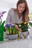 Jonge Vrouw die voor Houseplants binnen geven stock fotografie