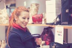 Jonge vrouw die voor nieuwe kleren winkelen stock fotografie