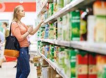 Jonge vrouw die voor sap in supermarkt winkelen Stock Foto's