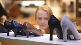 Jonge vrouw die voor schoenen winkelen stock videobeelden
