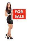 Jonge vrouw die a voor verkoopteken houden Royalty-vrije Stock Foto's