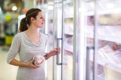 Jonge vrouw die voor vlees in een kruidenierswinkelopslag winkelen Stock Afbeeldingen