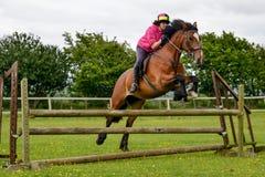 Jonge vrouw die voor vreugde op haar paard springen stock afbeeldingen