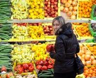 Jonge vrouw die voor vruchten en groenten winkelt Royalty-vrije Stock Afbeeldingen