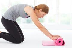 Jonge vrouw die voor yoga voorbereidingen treffen Stock Foto's