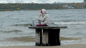 Jonge vrouw die in warme kleren op de oceaankust, op een houten rol, het drinken hete thee van een thermosfles zitten, die a gebr stock videobeelden