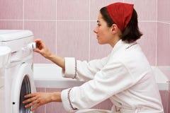 Jonge vrouw die wasmachine met behulp van Stock Afbeelding