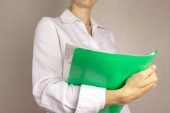 Jonge vrouw die in wit overhemd een dossieromslag in haar handen houden Bedrijfs concept royalty-vrije stock fotografie