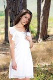 Jonge vrouw die in witte kleding in het hout glimlachen Royalty-vrije Stock Foto