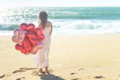Jonge vrouw die in witte kleding rode ballons op het strand houden Royalty-vrije Stock Afbeelding