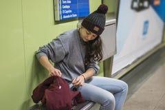Jonge vrouw die wolhoed dragen, controlerend laagzak, die in ondergronds wachten Royalty-vrije Stock Afbeeldingen