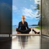 Jonge vrouw die yoga doen op het kantoor, het zand en het overzees op de vloer en de wolken in de hemel, tropische aard bij achte Royalty-vrije Stock Fotografie