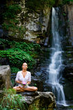 Jonge vrouw die yoga met lotusbloembloem doet Stock Fotografie