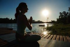 Jonge vrouw die yoga in ochtendpark doen dichtbij meer stock afbeeldingen