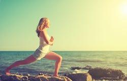 Jonge vrouw die yoga op strand doen Stock Afbeeldingen