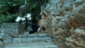 Jonge vrouw die yoga in park op steentrap buiten doen op blauwe mat stock footage