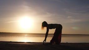 Jonge vrouw die yogaoefening doen die - haar yogamat op dichtbijgelegen overzees of oceaan openen zonsondergang of zonsopgang Het stock videobeelden