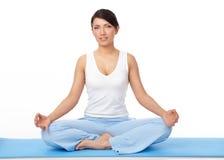 Jonge vrouw die yogaoefening op blauwe mat doet Stock Afbeeldingen