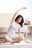 Jonge vrouw die yogaoefening op mat doet Royalty-vrije Stock Afbeeldingen