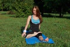 Jonge vrouw die yogaoefening op park doen Stock Afbeeldingen