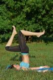 Jonge vrouw die yogaoefening op park doen stock foto's
