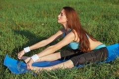 Jonge vrouw die yogaoefening op park doen stock foto