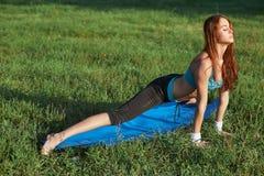 Jonge vrouw die yogaoefening op park doen stock afbeelding