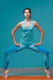 Jonge vrouw die yogaoefeningen doet stock fotografie