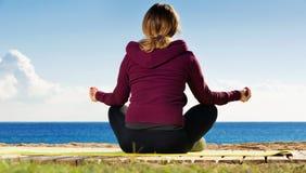 Jonge vrouw die youga doen bij strand Royalty-vrije Stock Foto's
