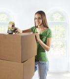 Jonge vrouw die zich aan een nieuw huis beweegt Stock Afbeeldingen