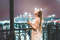 Jonge vrouw die zich alleen naast lichte pool bevinden stock afbeelding