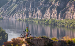 Jonge vrouw die zich in berg met fiets boven rivier bevinden Royalty-vrije Stock Foto