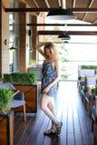 Jonge vrouw die zich bij koffie dichtbij groene palnts met opgeheven hand bevinden Stock Foto's