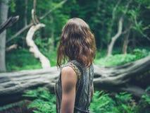 Jonge vrouw die zich in bos door gevallen boom bevinden Royalty-vrije Stock Afbeeldingen