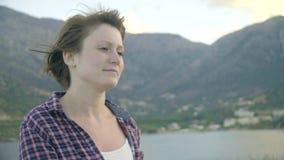 Jonge vrouw die zich bovenop een klip op een eiland bevinden die de oceaan bekijken Zonsondergang stock video